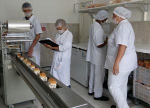 Nutricionista fiscalizando a produção de sanduíche da Kit Break.