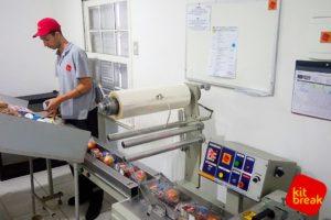 Funcionário operando a máquina embaladora na produção da Kit Break.