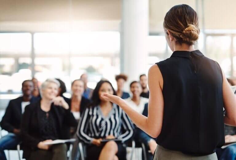 Organizacao de eventos. Mulher de frente para plateia em um evento.
